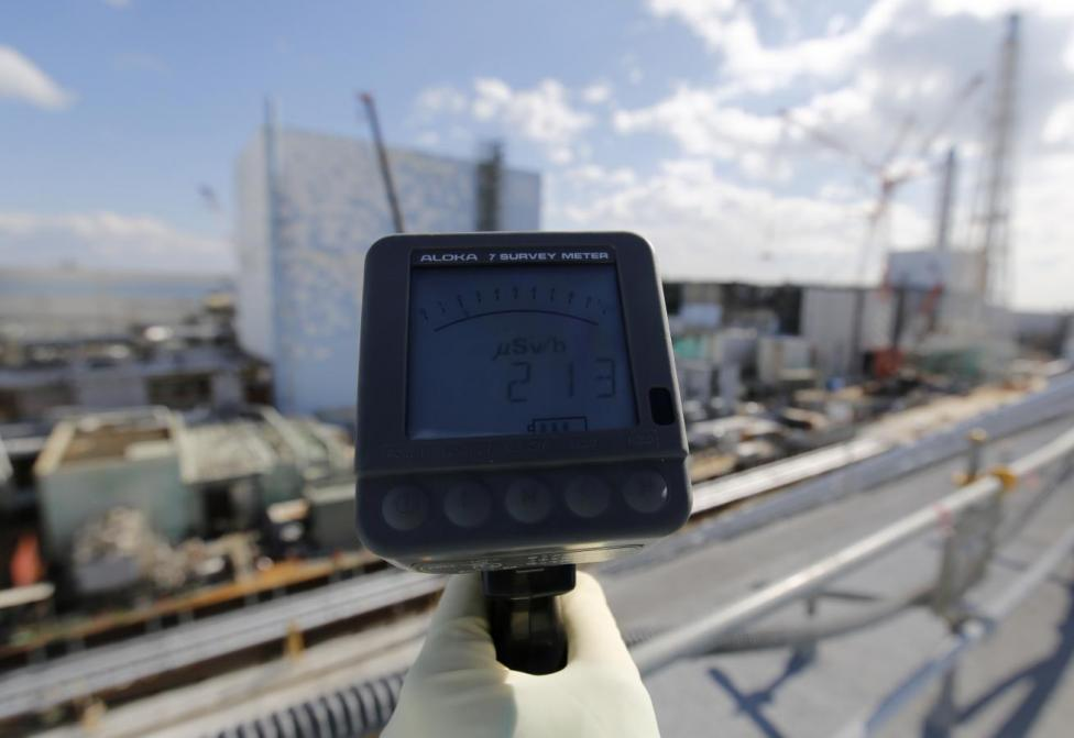 A Tokyo Electric Power Co. employee measures radiation level of 213 microsievert per hour in front of the No. 2 and No. 3 reactor buildings at TEPCO's tsunami-crippled Fukushima Daiichi nuclear power plant in Okuma town